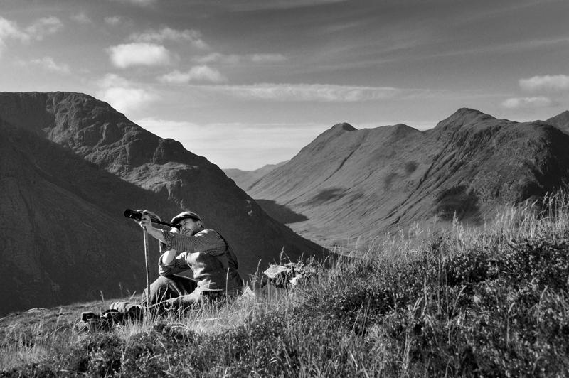 Black Corries, Glencoe. Deer stalker spying through telescope for stags. Black and white