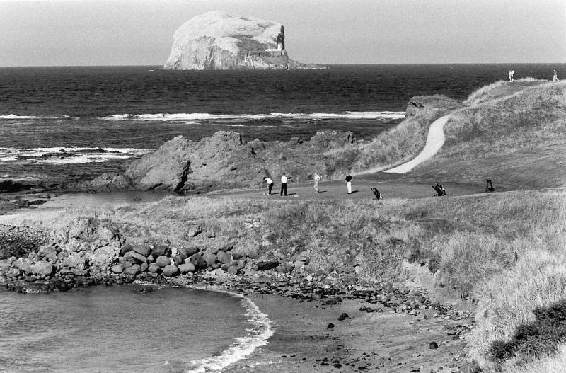 The Glen golf course with players. North Berwick. 13th green. Bass Rock.Black and white