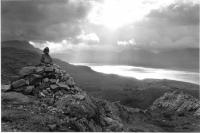 Stone cairn, Loch Torridon, atmospheric sky. Black and white.
