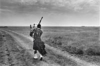 Dornoch. Lone Piper in empty landscape, rehearsing for Dornoch games. Black and white