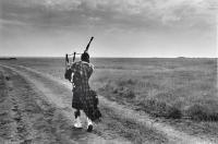 Dornoch. Lone Piper in empty landscape, rehearsing for Dornoch games. Black and white