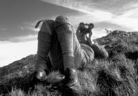Coulin Estate.Deer Stalker spying through binoculars. Traditional tweed clothing. Black and white
